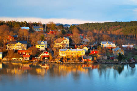 turku: Beautiful wooden colorful houses near water in Finland at sunset  Stock Photo