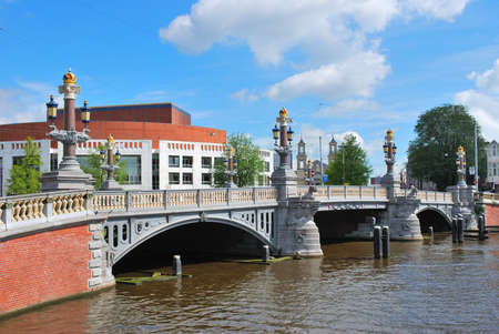 amstel: Amsterdam. Famous Blue bridge over the Amstel River and the building of Stopera on the background