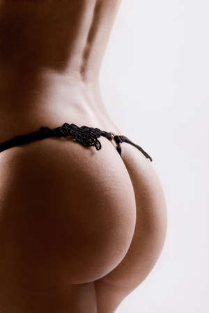 Las nalgas redondas con tanga de encaje negro Foto de archivo