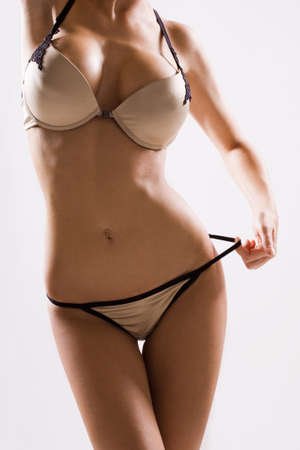 Close up of woman body in gold panties and bra Stock Photo