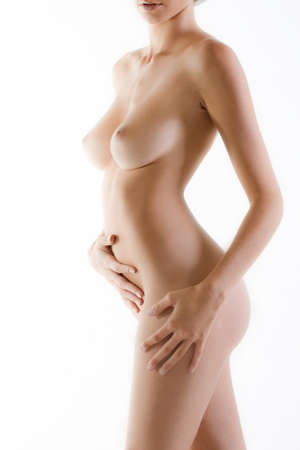 Lado del cuerpo desnudo femenino con el fondo blanco luminoso Foto de archivo
