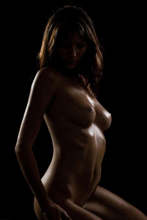 Nude shiny woman in the shadow Stock Photo