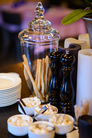 pepperbox: Bread sticks in a glass vase pepperbox plates saucers with sugar on a wooden table with decorative candles.