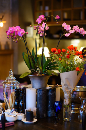 pepperbox: Orchid flowers in a decorative vase on a wooden table with candles and cutlery.