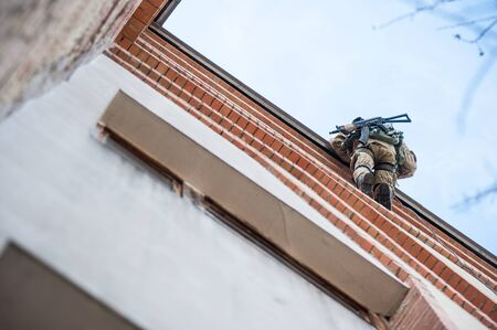 counterterrorism: Soldier with a gun on the edge of the roof coming down on a rope Stock Photo