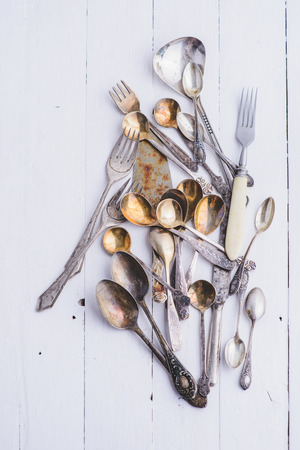 tarnished: Cutlery in vintage style on the wooden background - forks, spoons, knives. Stock Photo