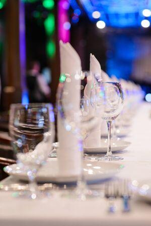 interrior: Wine glasses, plates and napkins in interrior of restaurant