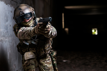 A soldier holding a gun in his hand and aiming