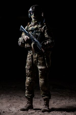 gun man: Soldier in camouflage with a rifle standing on a platoon and watches
