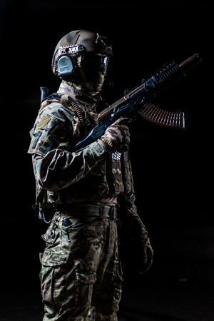 automatic machine: Equipped soldier standing in profile and holding automatic machine raised up Stock Photo