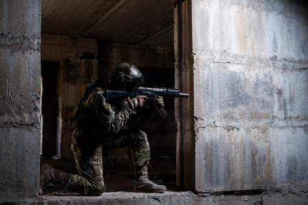 swat: Armed soldier in camouflage, mask and helmet aiming a rifle in a dark room