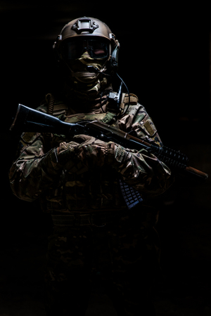technology security: Ranger in camouflage,mask and helmet  standing with arms and looking at the camera on black background