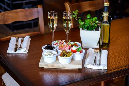 aperitive: Appetizers of vegetables, pickles, cheese and meat on a table with glasses of champagne Stock Photo