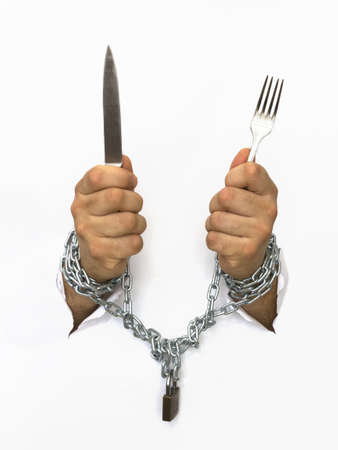 man hands handcuffed with chains holding knife and a fork Stock Photo - 9497711