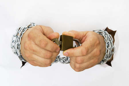 cuffed: man hands handcuffed with chains holding the lock and the key Stock Photo