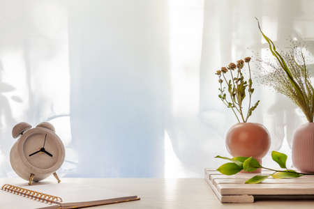 Photo of a desk with a concrete clock, an open notebook and vases with dried grasses on a background of sun-lit curtains