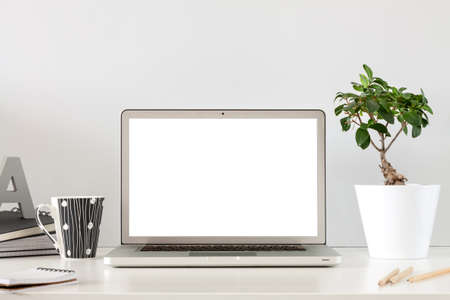 A business desk against a gray wall with an open laptop. Mockup screen.