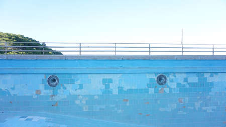 abandoned empty pool against blue sky background