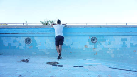 man with his back looking against blue background inside an empty pool
