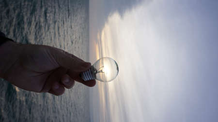 a hand holding a light bulb against sky background