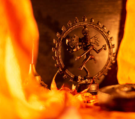 Close-up of a copper figurine of Shiva framed by orange drapes and lit by candle light 写真素材