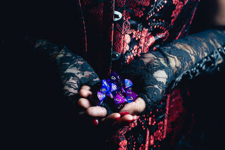 Women holding a bunch of purple rpg dice and wearing black lace gloves and a black and red corset