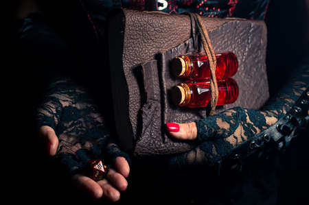 Women wearing black lace gloves holding a brown leather bound tome with glass bottles containing red liquid and a 20 sided die