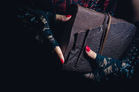 Women wearing black lace gloves holding a brown leather bound tome