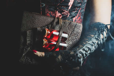 Someone wearing a black and red corset and black lace gloves holding a leather bound tome with two glass bottles with red liquid