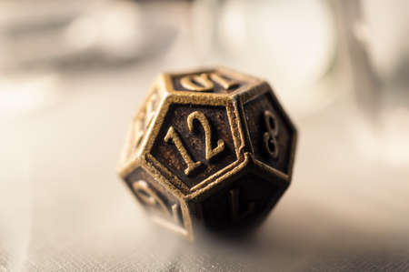 High contrast close-up image of a 12-sided role playing die surrounded by smoke. Stock Photo