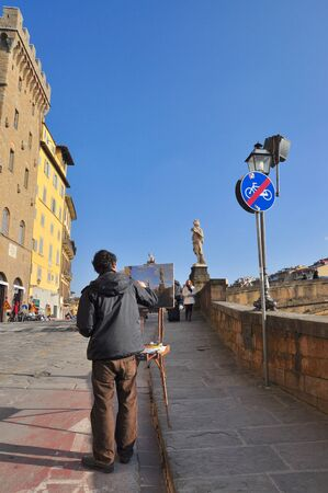Florence, Italy - February 23, 2011:  An artist painting the ornamental statues of the four seasons attached at the corners of the Ponte Santa Trinita.