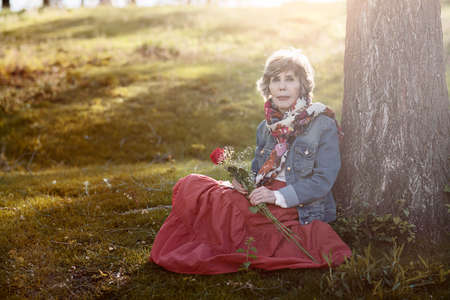 Happy senior woman sitting on the grass. Senior woman with a rose in her hand