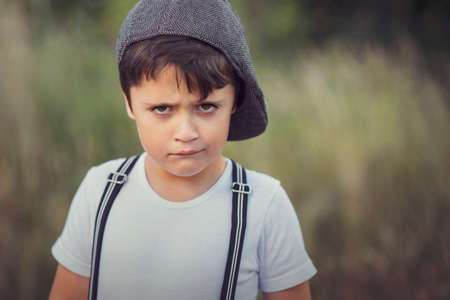 closeup of angry little boy with hat