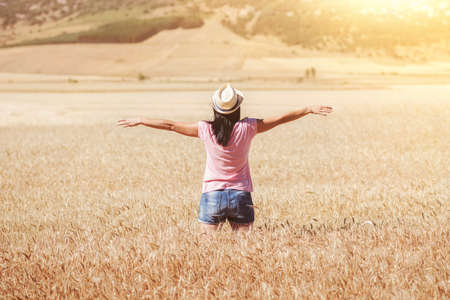 outer clothing: Woman in the wheat field. Cheerful young woman with hands up Stock Photo