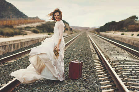 Pensive bride with a red suitcase on the train tracks Stock Photo