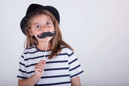 Beautiful cute little girl playing with mustache
