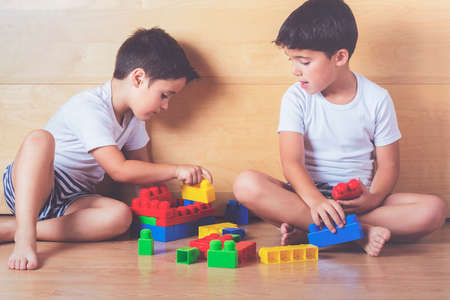 complicity: Brothers playing with blocks of colors