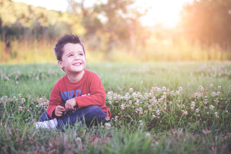 Happy and smiling child sitting on the grass