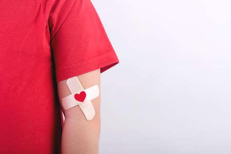 Niño con un corazón dibujado en su brazo. Concepto de donación de sangre