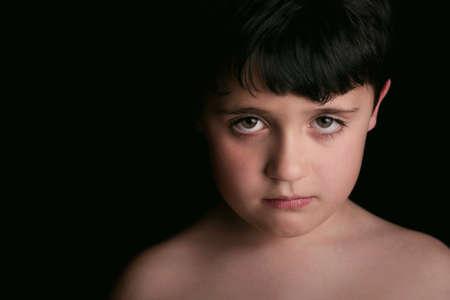 maltrato: niño triste sobre fondo negro
