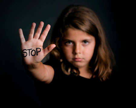 Angry girl showing hand signaling to stop violence Stock Photo