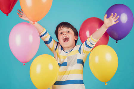 happy and smiling boy with colorful balloons