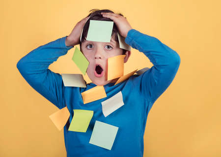 Portrait of kid with note papers stuck on body on a yellow background