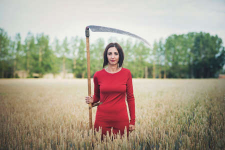 beautiful and mysterious girl with scythe outdoors