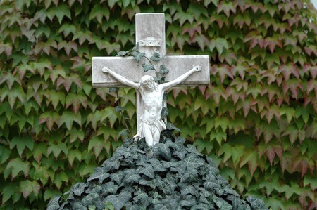 Grey marmoreal cross with trailing ivy Stock Photo