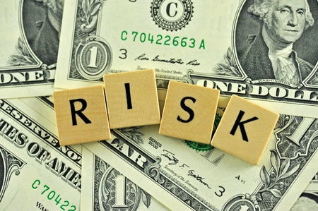 investment risks: Word risk in lettern on background of dollar banknotes