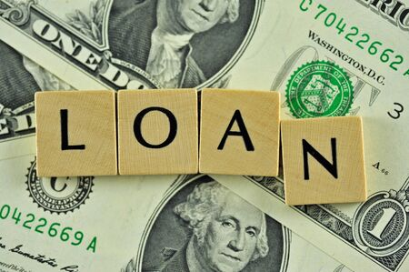 Word loan in lettern on background of dollar banknotes Stock Photo