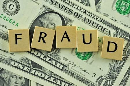 Woord fraude in lettern op de achtergrond van dollar biljetten