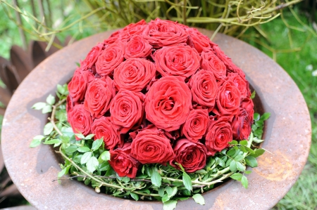 wreath of red roses in metal bowl Stock Photo