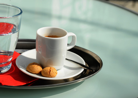 Espresso with a glass of water and cookies on a table Stock Photo